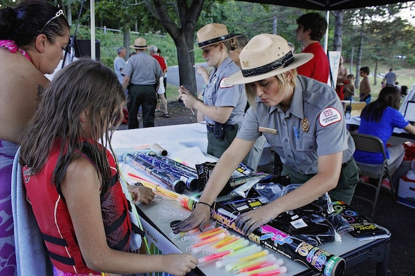 Olivia Mays, park ranger, U.S. Army Corps of Engineers, Raystown Lake, hands out glow sticks to participants of the 4th annual Glow Swim at Seven Points Beach, Aug. 6, 2016.