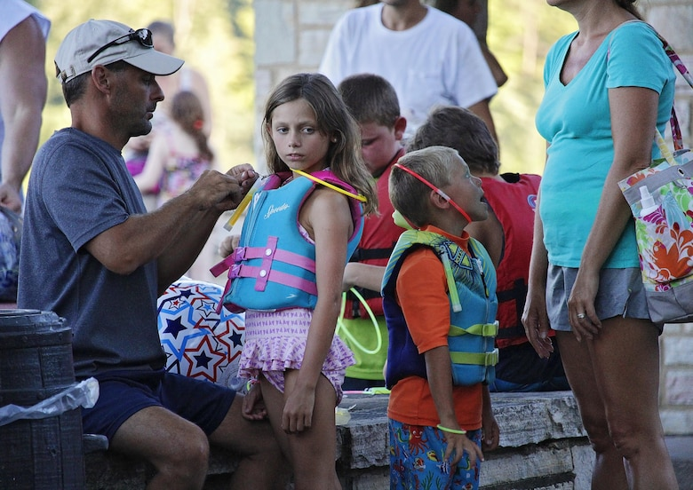 Parents wait alongside their children prior to the beginning of the 4th annual Glow Swim at Seven Points Beach on Saturday, Aug. 6, 2016.