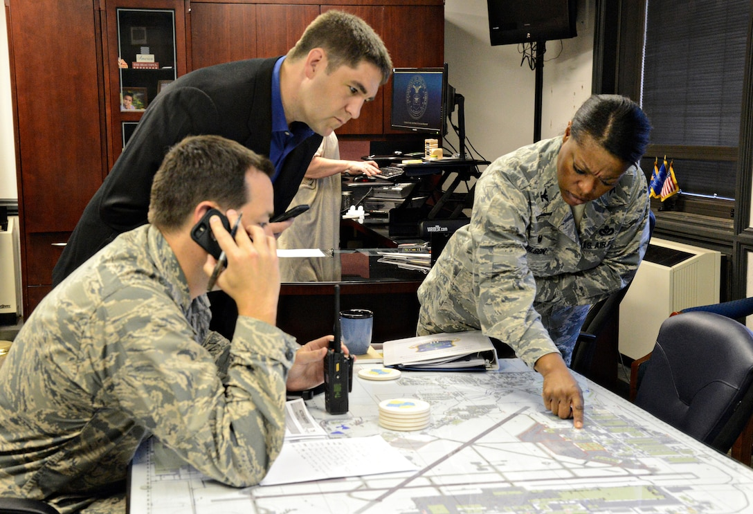72nd Air Base Wing leaders coordinated on-scene response personnel Aug. 9 during an active shooter exercise. From left, 72nd Security Forces Squadron Commander Lt. Col. Steven Ohlmeyer, OSI Det 114 Commander Special Agent Brandon Farley and 72nd ABW Commander Col. Stephanie Wilson directed all operations, including road closures, blocked perimeters and base lockdown procedures, while being briefed on real-time situations concerning the active shooters in the exercise. (Air Force photo by Kelly White)