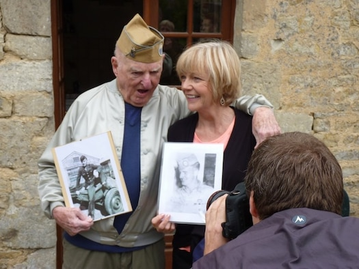 "William ""Bill"" Sullivan and wife, Elizabeth, hold up old photos of Bill at a reunion celebration in Normandy, France. The photos are from his time in service as a prisoner of war during World War II 1944-1945. (Courtesy Photo)"