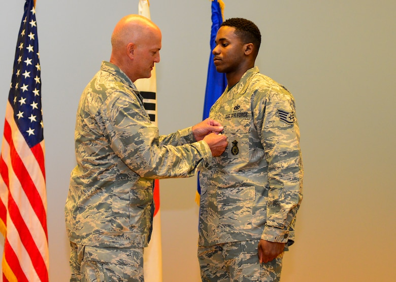 Staff Sgt. Rodney X. Dowell, 51st Security Forces Squadron information assurance NCO, is presented the Airman's Medal by Col. Andrew Hansen, 51st Fighter Wing commander, at Osan Air Base, Republic of Korea, July 29, 2016. In 2015, Dowell saved the lives of four people trapped in a burning vehicle while he was traveling to work early in the morning. (U.S. Air Force photo by Senior Airman Victor J. Caputo/Released)