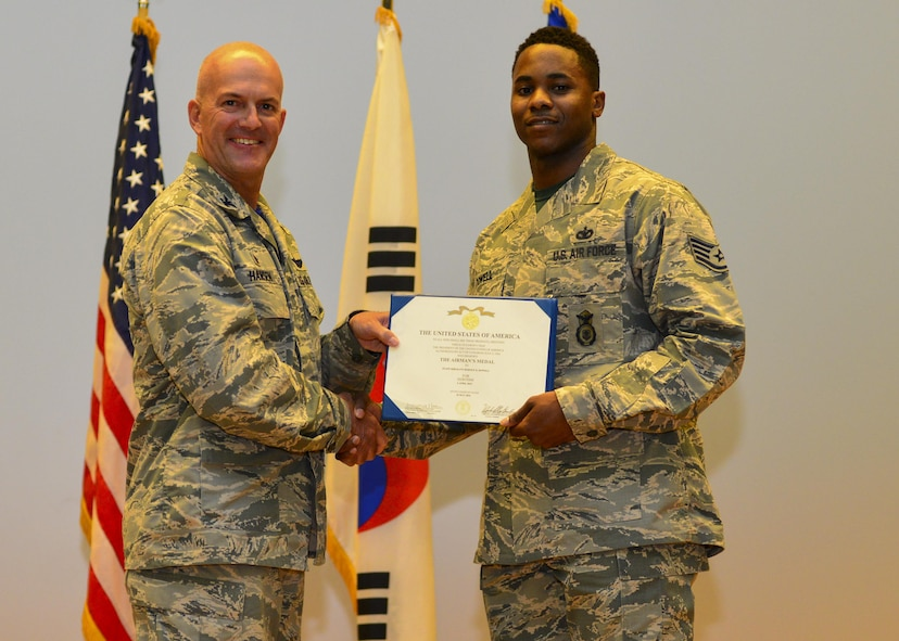 Staff Sgt. Rodney X. Dowell, 51st Security Forces Squadron information assurance NCO, poses with Col. Andrew Hansen, 51st Fighter Wing commander, after being presented with the Airman's Medal at Osan Air Base, Republic of Korea, July 29, 2016. The Airman's Medal is the highest non-combat medal awarded by the Air Force to individuals who distinguish themselves by heroic actions, usually at the voluntary risk of life. (U.S. Air Force photo by Senior Airman Victor J. Caputo/Released)