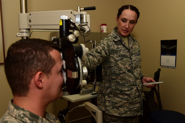 Capt. Kaylaen Evans, 460th Medical Group optometry element chief, administers a vision test to Tech. Sgt. Thomas Carrell, 460th MDG optometry NCO in charge, August 11, 2016, at the Veterans Affairs Joint Venture Buckley Clinic in Aurora, Colo. Vision tests are used to test a patient's clarity of vision and to see if corrective lenses are needed.(U.S. Air Force photo by Airman 1st Class Gabrielle Spradling/Released)