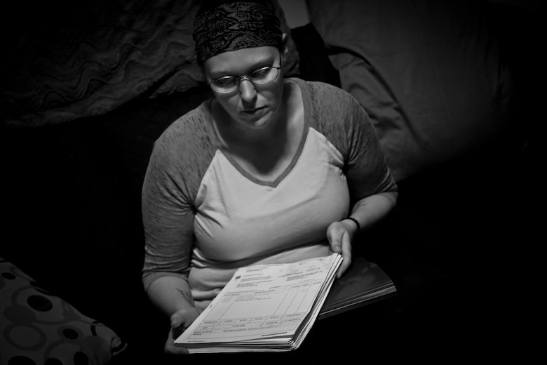 Rachel Miller, 30, looks at a stack of unpaid medical bills, July 19, 2016. Miller and her boyfriend Matt Nichol are both on disability, and live in a small one bedroom apartment in Cortland, N.Y. Nearly one in three residents of Cortland are at or below the poverty line. Miller and Nichol attended the Healthy Cortland Innovative Readiness Training event aimed at Cortland residents, which included military service members providing no cost medical, dental, optometry, and veterinary care. (U.S. Air National Guard photo by Tech. Sgt. Matt Hecht/Released)