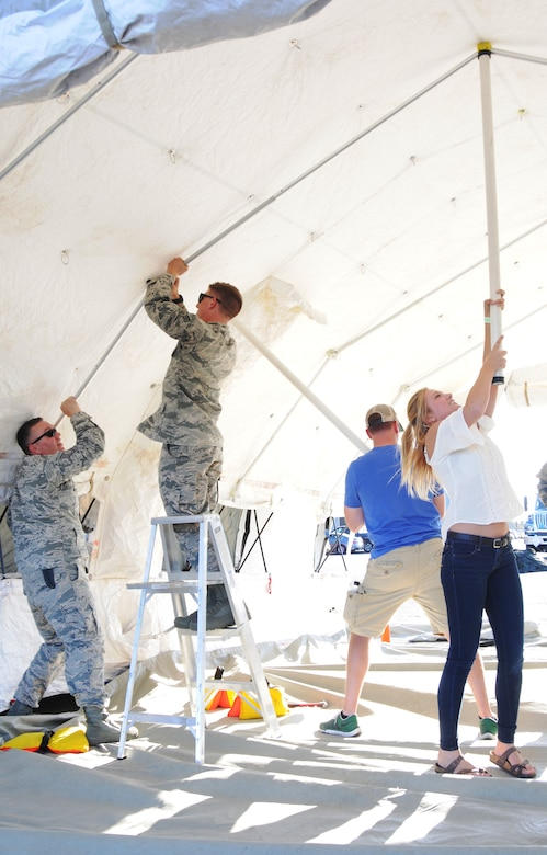 Members of the 142nd Fighter Wing set up a tent used to display historical items as part of the 75th Anniversary of the Oregon Air National Guard during the Oregon International Air Show in Hillsboro, Ore., Aug. 5, 2016. (U.S. Air National Guard photo by Tech. Sgt. John Hughel, 142nd Fighter Wing Public Affairs/Released).