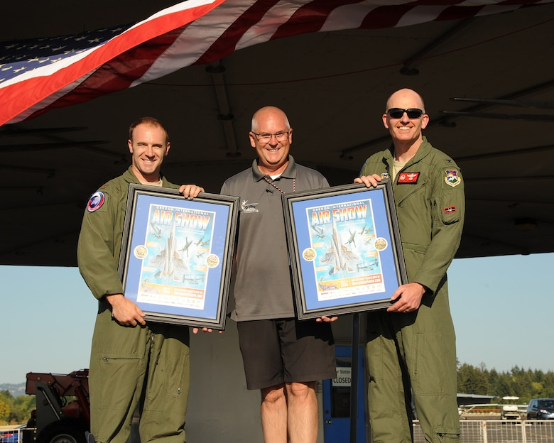 "Oregon International Air Show President Bill Braack, center, presents posters to Maj. William Sullivan assigned to the 173rd Fighter Wing, left, and 142nd Fighter Wing Commander Paul Fitzgerald, right, during the afterhours ""All Call"" cerebration held at the Hillsboro International Airport, Ore., Aug. 6, 2016. (U.S. Air National Guard photo by Master Sgt. Shelly Davison, 142nd Fighter Wing Public Affairs/Released)."