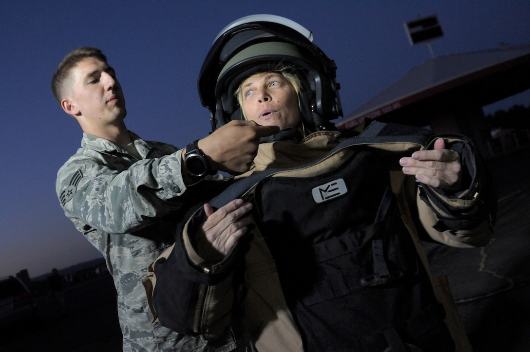 Oregon Senior Airman Alec Camp, an explosive ordinance disposal technician assigned to the 142nd Civil Engineer Squadron helps Sherrie Speck try on protective equipment used to secure explosive materials during the Oregon International Air Show, Hillsboro, Ore., Aug. 5, 2016. (U.S. Air National Guard photo by Tech. Sgt. John Hughel, 142nd Fighter Wing Public Affairs/Released).