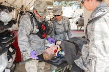 (From the left) Maj. Robert J. Ochsner, basic life support physician, Capt. Alex P. Peterson, nurse practitioner and 2nd Lt. Margaret J. Mazzarello, nurse practitioner, all assigned to the 140th Medical Group, Buckley Air Force Base, Colo. examine a patient in triage for internal and external wounds during the joint exercise evaluation (EXEVAL), held at Camp Rilea, Warrenton, Oregon, on Aug. 4, 2016. The EXEVAL ran for five days in a crawl, walk, run sequence, where they started off slowly, then transitioned into rapid response on evaluation day. (U.S. Air National Guard photo by Staff Sgt. Bobbie Reynolds)