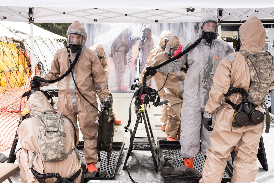 Colorado Army National Guard Soldiers move through the decontamination tent, where they are sprayed down thoroughly and checked for any signs of chemical, biological, radiological or nuclear residual, in an effort to train for a joint exercise evaluation (EXEVAL), where they'll be evaluated for war time readiness at Camp Rilea, Warrenton, Oregon, on Aug. 3, 2016. The EXEVAL scenerios changed every day, giving Soldiers and Airmen the opportunity to practice in multiple atmospheres with various personnel. (U.S. Air National Guard photo by Staff Sgt. Bobbie Reynolds)