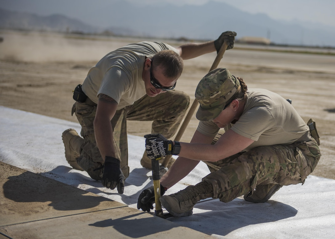 Master Sgt. Cassandra Doub, the 455th Expeditionary Civil Engineer Squadron first sergeant, and Staff Sgt. Andrew Perna, a 455th ECES maintenance and equipment craftsman, secure AM-2 matting with a hammer at Bagram Airfield, Afghanistan, Aug. 11, 2016. AM-2 matting is used to form runways, taxiways, parking and other areas required for aircraft operations and maintenance.  (U.S. Air Force photo/Senior Airman Justyn M. Freeman)