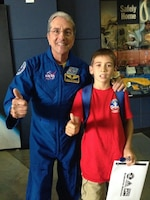 Conner Mullins pauses for a picture with NASA astronaut Don Thomas at Space Camp graduation at the U.S. Space & Rocket Center.