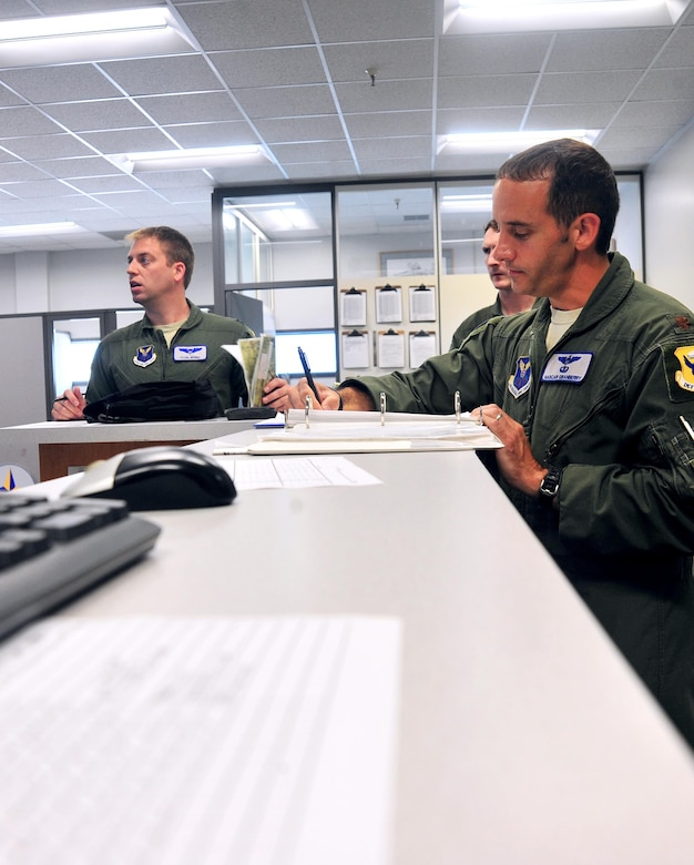 U.S. Air Force Maj. Michael Granberry, the 394th Combat Training Squadron T-38 Talon assisted director of operations of the Companion Trainer Program (CTP), signs off pre-flight requirements before piloting a T-38 Talon Aircraft at Whiteman Air Force Base, July 12, 2016. Pilots undergo a flight briefing that includes a weather report and other aircraft in airspace before flying.