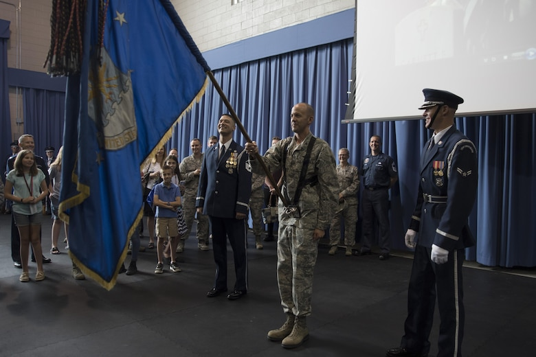 Col. E. John Teichert, 11th Wing and Joint Base Andrews commander, gets instructed on how to properly hold the Air Force flag by members of the U.S. Air Force Honor Guard at Joint Base Anacostia-Bolling in Washington, D.C., Aug. 9, 2016. The purpose of the visit was for Teichert and Chief Master Sgt. Beth Topa, 11th WG command chief master sergeant, to become more familiar with the U.S. Air Force Band and Honor Guard missions. (U.S. Air Force Photo by Airman 1st Class Rustie Kramer)