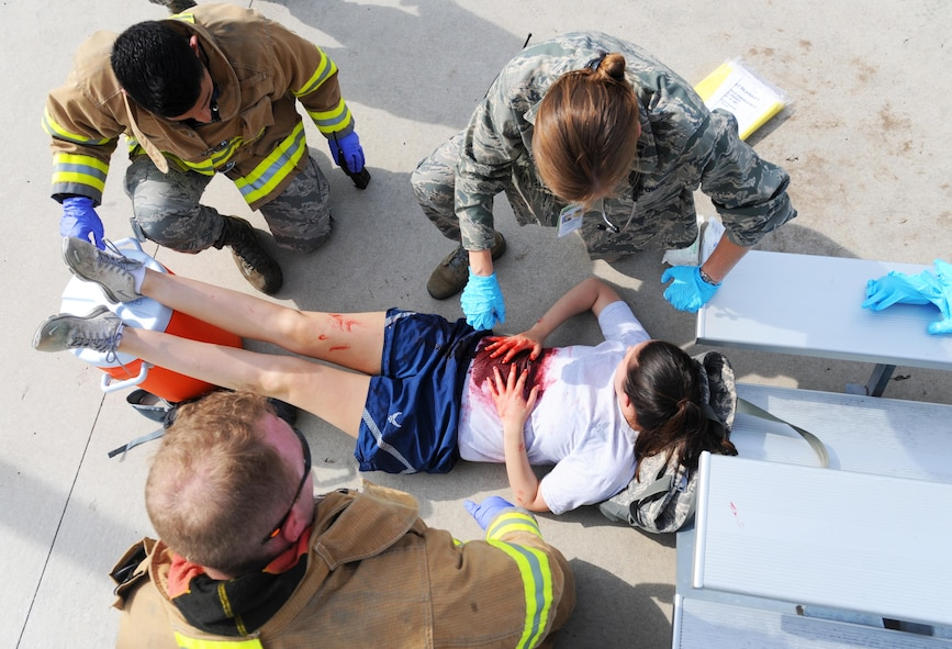 """U.S. Air Force Capt. Kallyn Harencak, a 509th Medical Operations Squadron flight surgeon, and members of the 509th Civil Engineer Squadron Fire Department treat Staff Sgt. Jaclyn McDuffie, a 509th Bomb Wing plans and programs assistant, for simulated wounds during an active shooter exercise at Whiteman Air Force Base, Mo., Aug. 5, 2016. The """"victims"""" had moulage wounds put on them so first responders could determine the urgency of each injury."""