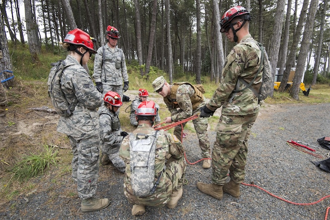 Soldiers and airmen listen as an evaluator explains how to tie a rope around a victim being hoisted from a tower of rubble during a joint exercise evaluation at Camp Rilea in Warrenton, Ore., Aug. 2, 2016. The soldiers and airmen, assigned to the Colorado National Guard's search and extraction teams, will practice search and extraction techniques and medical procedures to save lives in the event of a domestic emergency. Air National Guard photo by Staff Sgt. Bobbie Reynolds