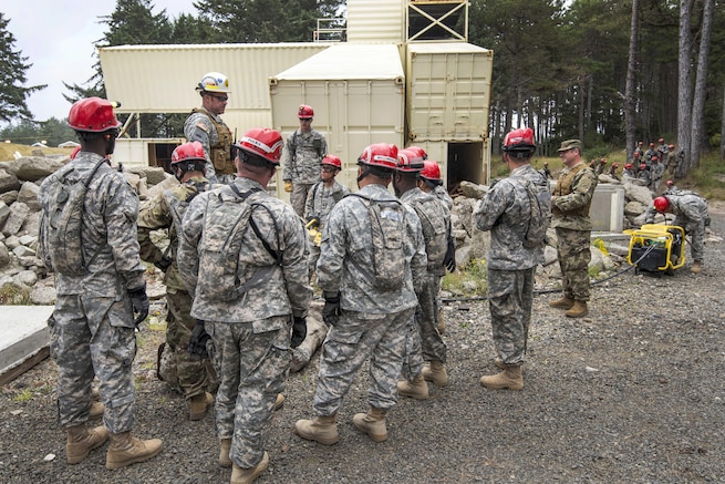 Soldiers and airmen listen to an evaluator explain how to saw through piles of cement rubble after a simulated chemical attack during a joint exercise evaluation at Camp Rilea in Warrenton, Ore., Aug. 2, 2016. Air National Guard photo by Staff Sgt. Bobbie Reynolds