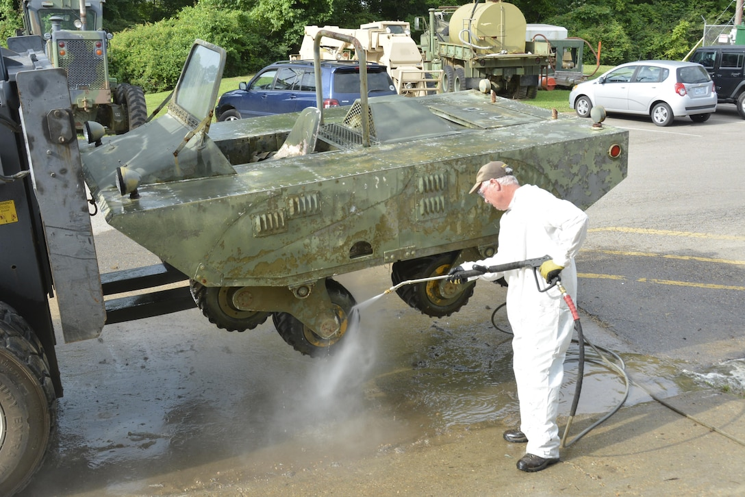 "Terry Winschel, historian for the U.S. Army Engineer Research and Development Center, uses a power washer to clean off a unique prototype military vehicle designed with ""tri-star"" wheels. Winschel is on a mission to preserve and restore historic prototypes tested by ERDC since the 1960s."