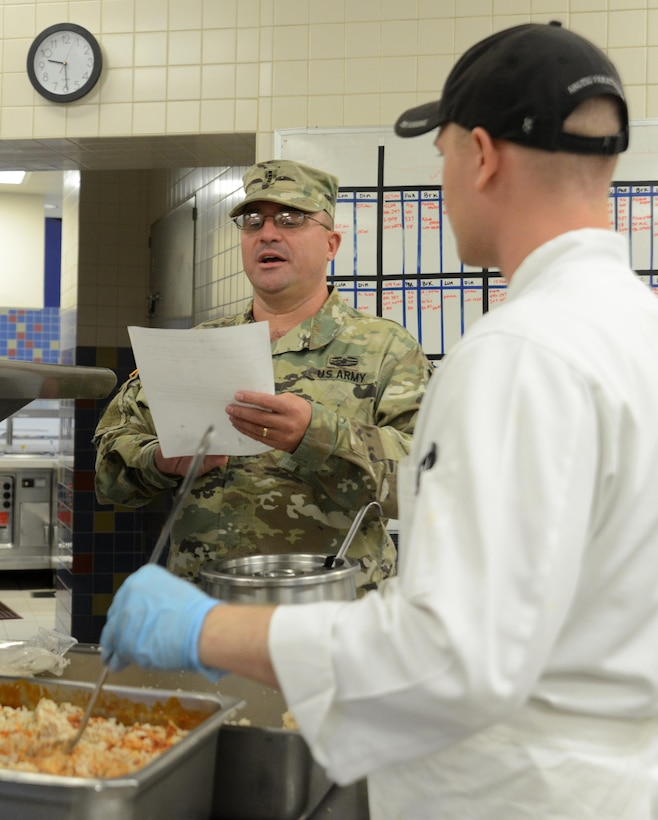Chief Warrant Officer 4 Curtis Steineke, 402nd Army Field Support Brigade regional food program manager and a Philip A. Connelly competition evaluator, inspects food preparation at the Wilderness Inn dining facility at Joint Base Elmendorf-Richardson, Alaska, Aug. 3, 2016. The Philip A. Connelly award provides recognition for excellence in the preparation and serving of food in Army dining facilities and during field kitchen operations. (U.S. Air Force photo by Airman 1st Class Christopher R. Morales)