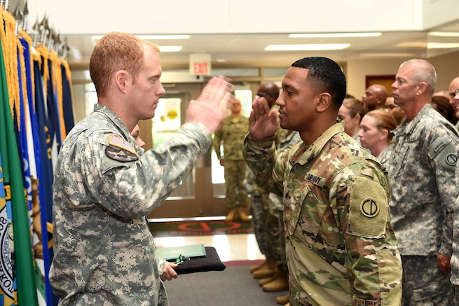 Captain Russell Litko, Headquarters & Headquarters Company commander, 85th Support Command, left, returns a salute to Sgt. Roje Rogers, Supply Sergeant, 85th Support Command, during an award ceremony presentation during the command's battle assembly, on Aug. 7, 2016. Rogers received the Army Commendation Medal during the ceremony.