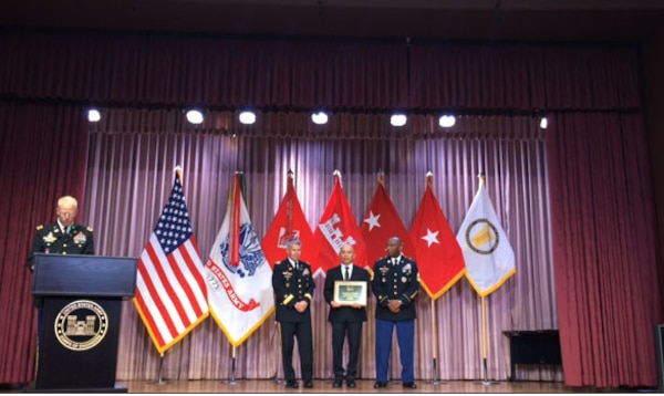 Nic Sison, a construction representative with the Middle East District, accepts the USACE Hard Hat of the Year Award Aug. 5.