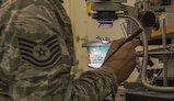 Tech. Sgt. Dustin Allen, Air Force repair enhancement program technician, inspects a motherboard inside the Air Force repair enhancement program shop Aug. 3, 2016, on Kadena Air Base, Okinawa, Japan. Members of the AFREP shop are trained on micro–soldering at Davis-Monthan Air Force Base , Arizona, allowing them to work on parts that other shops in the Air Force are unable to fix.