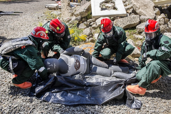 Airmen load a medical mannequin into a collection bag during training at Camp Rilea, Warrenton, Ore., Aug. 4, 2016. The airmen, assigned to the Colorado National Guard's 140th Fatality Search and Rescue Team, function as a recovery team, helping families find closure after properly identifying those who have lost their lives. Air National Guard photo by Staff Sgt. Bobbie Reynolds