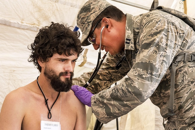 Air Force Capt. Thomas J. Dishion checks the vital signs of a role- playing casualty during a joint exercise evaluation at Camp Rilea, Warrenton, Ore., Aug. 5, 2016. Dishion is a physician assistant assigned to the Colorado National Guard's 140th Medical Group. Air National Guard photo by Staff Sgt. Bobbie Reynolds