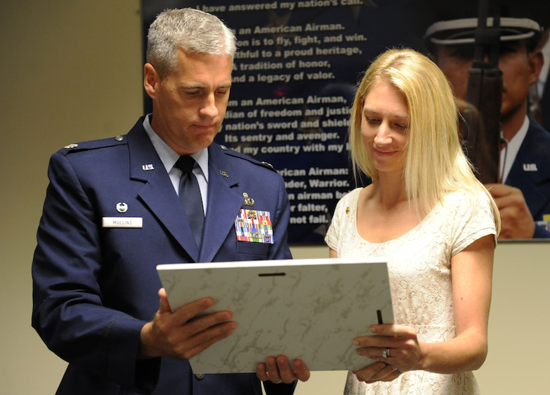Lt. Col. Steven Mullins, 334th Training Squadron commander, presents Heather Gray Blalock, wife of the late Maj. W. David Gray, with a plaque during a room dedication ceremony to honor her late husband Aug. 8, 2016, on Keesler Air Force Base, Miss. Gray served for several years as an airfield operations officer and was killed in action in Afghanistan on Aug. 8, 2012. A tower lab training room was dedicated during the event. (U.S. Air Force photo by Kemberly Groue/Released)