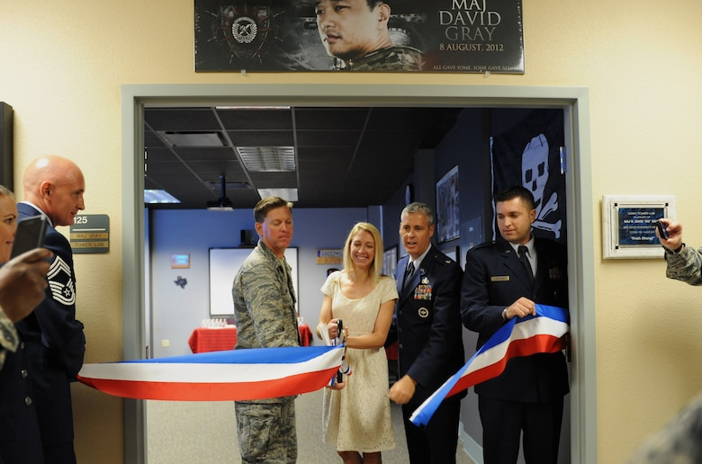 Col. C. Mike Smith, 81st Training Wing vice commander, Heather Gray Blalock, wife of the late Maj. W. David Gray, Lt. Col. Steven Mullins, 334th Training Squadron commander, and Capt. Gregory Birdsong, 334th TRS instructor supervisor, participate in a ribbon cutting ceremony at Cody Hall to honor Blalock's late husband Aug. 8, 2016, on Keesler Air Force Base, Miss. Gray served for several years as an airfield operations officer and was killed in action in Afghanistan on Aug. 8, 2012. A tower lab training room was dedicated during the event. (U.S. Air Force photo by Kemberly Groue/Released)