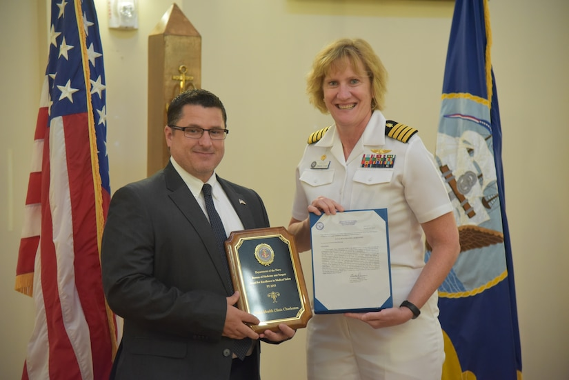 Cory VanDyke, safety officer for Naval Health Clinic Charleston, receives the 2015 Award for Excellence in Medical Safety from NHCC commanding officer Capt. Elizabeth Maley on behalf of the Department of the Navy Bureau of Medicine and Surgery Aug. 5, 2016  at NHCC, JB Charleston - WS.