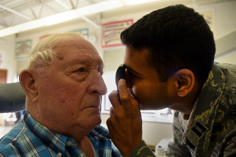 U.S. Air Force Capt. Saurin Patel, 108th Medical Group, checks Ira Holl's eyes to see what prescription he will need during the Healthy Cortland event at Homer Intermediate School in Homer, N.Y., July 19, 2016. Service members provided no cost medical, dental, optometry, and veterinary care to local citizens. (U.S. Air National Guard photo by Senior Airman Julia Santiago)