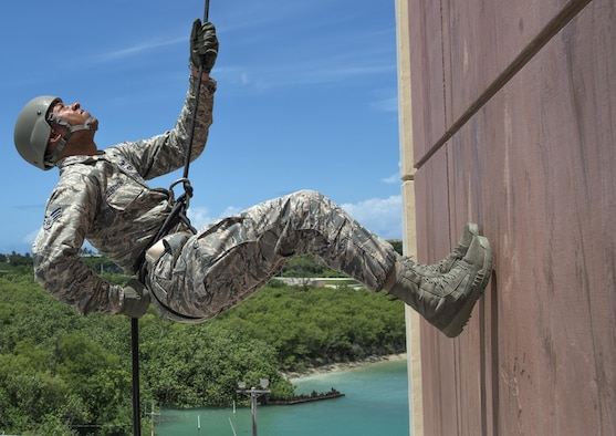Senior Airman Brandon Jefferson, 554th RED HORSE Squadron operations control, awaits instruction while rappelling down a 90-foot tower Aug. 9, 2016, at Naval Base Guam. The purpose of the rappel training was to provide real-world training for 554th RHS members. RED HORSE units provide a highly responsive force to support contingency, peacetime and humanitarian operations world-wide. (U.S. Air Force photo by Master Sgt. JT May III)