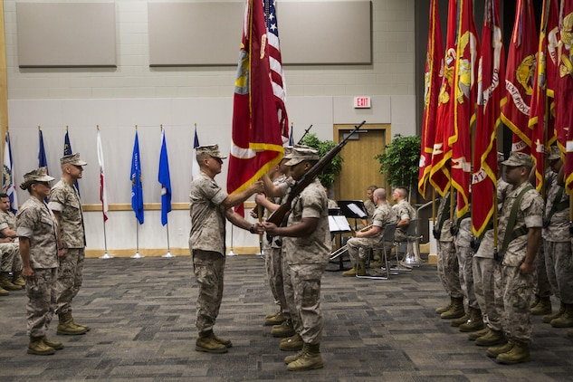 Sgt. Maj. William J. Grigsby (center), Sergeant Major of Force Headquarters Group, Marine Forces Reserve, takes the colors from the FHG color guard during the change of command ceremony at the Federal City Auditorium, New Orleans, Aug. 13, 2016. The passing of the colors symbolizes the transition from one commander to the other. (U.S. Marine Corps photo by Lance Cpl. Melissa Martens/ Released)