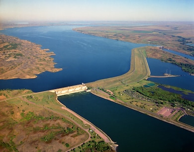 """Big Bend Dam is located near Chamberlain, S.D., at River Mile 987.4. Although, the dam has a unique bend in its embankement,  Big Bend Dam takes its name from the unique bend in the Missouri River seven miles upstream from the dam. At this point in its course, the Missouri makes almost a complete loop, traveling 25 miles before returning to the """"neck"""" where the land is only about one mile wide."""