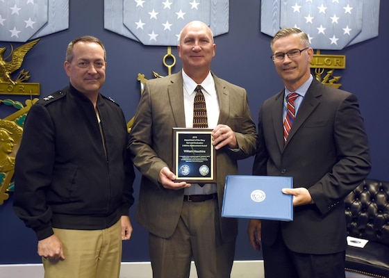 Mr. William Houchins, Naval Surface Warfare Center Dahlgren Division (NSWCDD), center, is awarded the Department of the Navy Test and Evaluation Lifetime Achievement Award from Rear Adm. Mathias Winter N84, and Mr. Rick Quade, SES, DASN (RDT&E)/N84C.