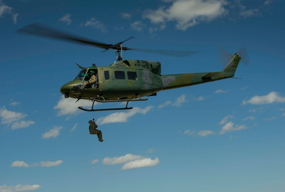 A Team Minot Airman is hoisted in a UH-1N Iroquois during survival, evasion, resistance and escape training in Garrison, N.D., Aug. 11, 2016. The all-day training focused on search and rescue situations for aircrew members. (U.S. Air Force photo/Senior Airman Apryl Hall)