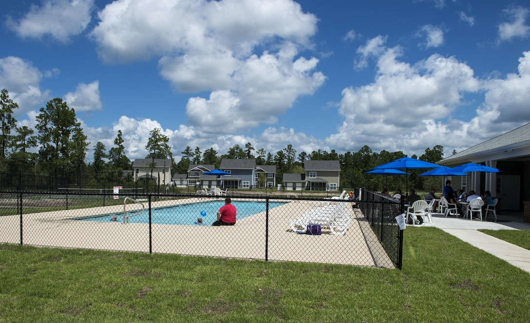 Residents eat barbeque and enjoy the pool during the grand opening of the community center in Azalea Commons, Aug. 12, 2016, in Valdosta, Ga. Azalea Commons houses 90 military families between E-1 and O-5. (U.S. Air Force photo by Airman 1st Class Janiqua P. Robinson)