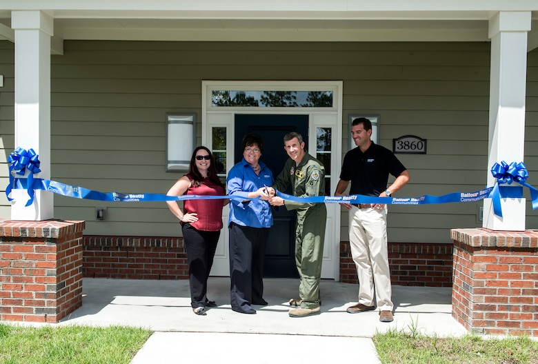 Devona Hathcock, center left, community manager for a local real estate company, and U.S. Air Force Col. Thomas Kunkel, center right, 23d Wing commander, cut a ribbon Aug. 12, 2016, in Valdosta, Ga. The ceremonial ribbon cutting celebrated the opening of the community center in the recently-opened Azalea Commons housing area. After the ceremonial ribbon cutting, attendees were served barbeque, toured the new community center and took a dip in the pool. (U.S. Air Force photo by Airman 1st Class Janiqua P. Robinson)