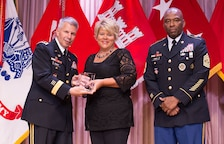 Kris Fairbanks, center, receives the Family Readiness Outstanding Team Achievement Award from Lt. Gen. Todd T. Semonite, Chief of Engineers and U.S. Army Corps of Engineers commanding general and Command Sgt. Maj. Antonio S. Jones during the 2016 National Awards Ceremony  in Washington, D.C., Aug. 4 Fairbanks accepted the award on behalf of the Mississippi Valley Division team. She also was the 2015 Family Readiness Individual Excellence Award recipient.