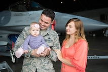 U.S Air Force Staff Sgt. John Dunlap, a 35th Aircraft Maintenance Unit F-16 Fighting Falcon crew chief deployed from Kunsan Air Base, Republic of Korea, his wife Jennifer and 6-month-old baby Evelyn, tour the Thunderdome while visiting after his shift Aug. 11, 2016, during RED FLAG-Alaska 16-3, at Eielson Air Force Base, Alaska. Jennifer and the baby met Dunlap in Alaska to visit for the first time in the U.S. while he has been stationed at Kunsan, a remote duty location, where families are not permitted to reside with their sponsors. (U.S. Air Force photo by Staff Sgt. Shawn Nickel)