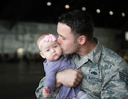 U.S. Air Force Staff Sgt. John Dunlap, a 35th Aircraft Maintenance Unit F-16 Fighting Falcon crew chief deployed from Kunsan Air Base, Republic of Korea, kisses his 6-month-old baby Evelyn after his shift Aug. 11, 2016, during RED FLAG-Alaska (RF-A) 16-3 at Eielson Air Force Base, Alaska. Dunlap's family took the time he was in the U.S. to visit during RF-A, a Pacific Air Forces commander-directed exercise, which is vital to maintaining peace and stability in the Indo-Asia-Pacific area of responsibility. (U.S. Air Force photo by Staff Sgt. Shawn Nickel)