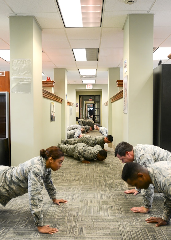 Members of the 628th Comptroller Squadron do push-ups together in their office at Joint Base Charleston – Air Base, S.C. Aug. 9, 2016. The 628th CPTS was recognized by the Health and Wellness Center (HAWC) as one of the healthiest and most fit squadrons on base. (U.S. Air Force photo by Airman 1st Class Thomas T. Charlton)