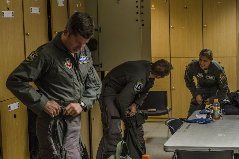 U.S. Air Force pilots from the 55th Fighter Squadron, Shaw Air Force Base, S.C., attach their g‐suites in preparation for a familiarization flight at Nellis Air Force Base, Nev., Aug. 13, 2016. The g‐suite is used to squeeze blood from the legs into the head while at high speeds enabling the pilots to fly longer hours. (U. S. Air Force photo by Tech. Sgt. Frank Miller/Released)