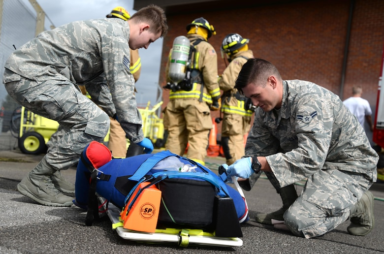 U.S. Air Force Staff Sgt. Jonathon Powell, left, and U.S. Air Force Airman 1st Class Andrew Giles, both 48th Medical Operations Squadron emergency services technicians, strap down a manikin patient in preparation for transportation Aug. 11, 2016, during an exercise on RAF Mildenhall, England. The medics simulated giving the patient supplemental oxygen and established neck and back support by using spider straps to secure the body on the board. (U.S. Air Force photo by Senior Airman Justine Rho)