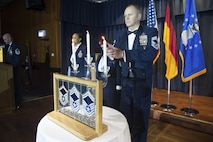 U.S. Air Force Chief Master Sgt. Scott Chord, 702nd Munitions Support Squadron chief enlisted manager, center right, lights a candle during a senior NCO induction ceremony at Club Eifel on Spangdahlem Air Base, Germany, Aug. 12, 2016. Senior NCOs lit corresponding candles symbolizing the achievement into the top tier enlisted ranks. (U.S. Air Force photo by Airman 1st Class Preston Cherry/Released)