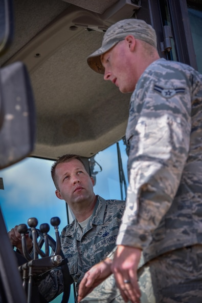 """Chief Master Sgt. Edwin Ludwigsen, 52nd Fighter Wing command chief, receives instruction from Airman 1st Class Tyler Carrigan, 52nd Civil Engineer Squadron, on how to operate heavy equipment as part of an """"out and about"""" visit with 52nd CES at Spangdahlem Air Base, Germany, Aug. 11, 2016. (U.S. Air Force photo by Tech. Sgt. Christopher Parr)"""
