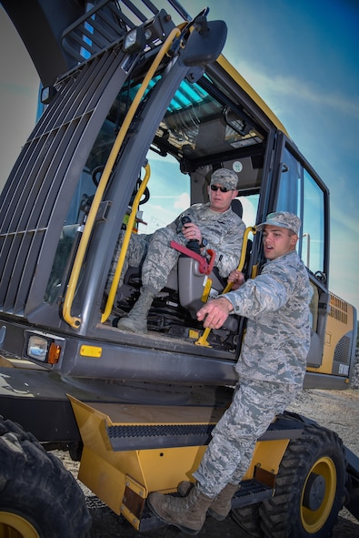 "Col. Joseph McFall, 52nd Fighter Wing commander, is given instructions by Airman 1st Class Michael Panarello, 52nd Civil Engineer Squadron, on how to operate an excavator during an ""out and about"" visit at Spangdahlem Air Base, Germany, Aug. 11, 2016. The visit allowed Spangdahlem leadership to learn about the mission of the 52 CES heavy equipment operators, or ""Dirt Boyz."" (U.S. Air Force photo by Tech. Sgt. Christopher Parr)"