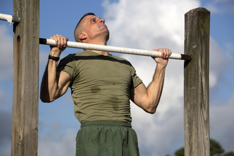 Col. Mark T. Palmer participates in a pull-up event during the 75th anniversary field meet competition at Marine Corps Air Station Cherry Point, N.C., Aug. 12, 2016. Headquarters and Headquarters Squadron, Marine Corps Air Station Cherry Point, and Marine Wing Headquarters Squadron 2, 2nd Marine Aircraft Wing, Marines of all ranks and ages came together to compete in numerous events testing their strength, teamwork and unit spirit. Some of the events the competitors participated in include: an all ranks relay, rifle relay race, unit soccer, a 7-ton pull and more. Palmer is the chief of staff for 2nd MAW. (U.S. Marine Corps photo by Cpl. N.W. Huertas/Released)