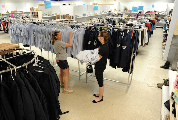 Staff. Sgts. Erin Shaw and Jessica Hegler, 335th Training Squadron students, hang clothing items at the Airman's Attic Aug. 12, 2016, on Keesler Air Force Base, Miss. The Airman's Attic assists enlisted members in pay grades E-1 through E-6 with obtaining basic household items at no cost. It is located at the corner of Meadows Drive and 1st Street, next to the Keesler Thrift Shop. (U.S. Air Force photo by Kemberly Groue/Released)