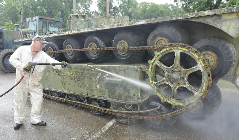 """Historian Terry Winschel power-washes the """"Airoll,"""" one of the vehicle prototypes belonging to the Engineer Research and Development Center in Vicksburg, Mississippi, where mobility tests have been conducted since the late 1960s. Many of the rare prototype vehicles Winschel is trying to preserve are so unusual, parts – like tires for an Airoll – are difficult to come by."""